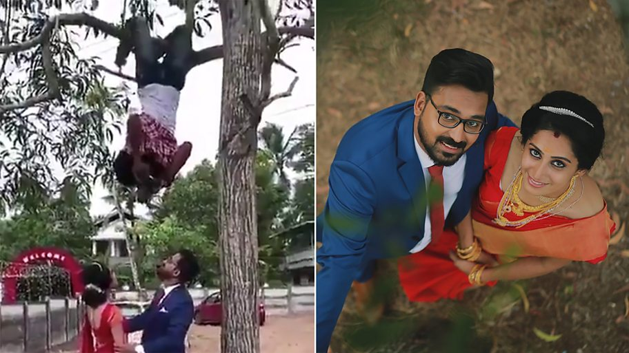 A wedding photographer hangs from a tree to take a picture