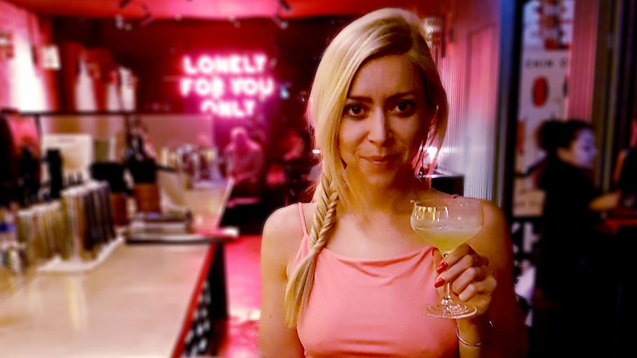 Nichi Hodgson standing in a bar with a cocktail