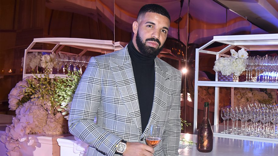 Drake in a grey suit jacket