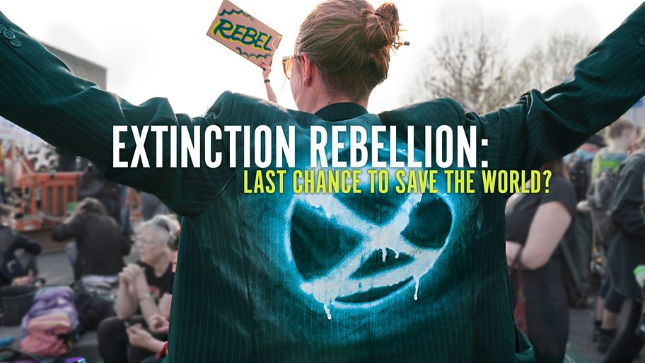 A young woman stands with arms outstretched in front of a crowd. Her jacket has the Extinction Rebellion hourglass logo on it.