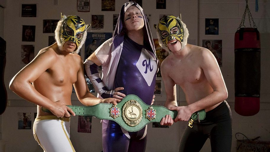 A group of wrestlers hold a belt