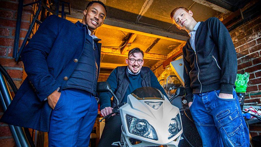 Three men in a garage