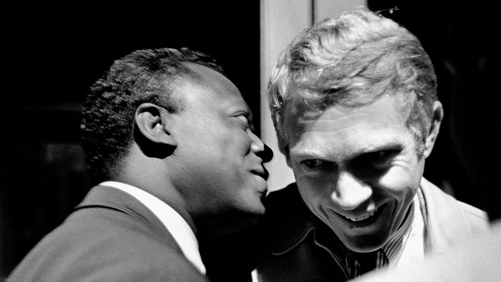 Miles davis talks to steve mcqueen at the 1963 monterey jazz festival