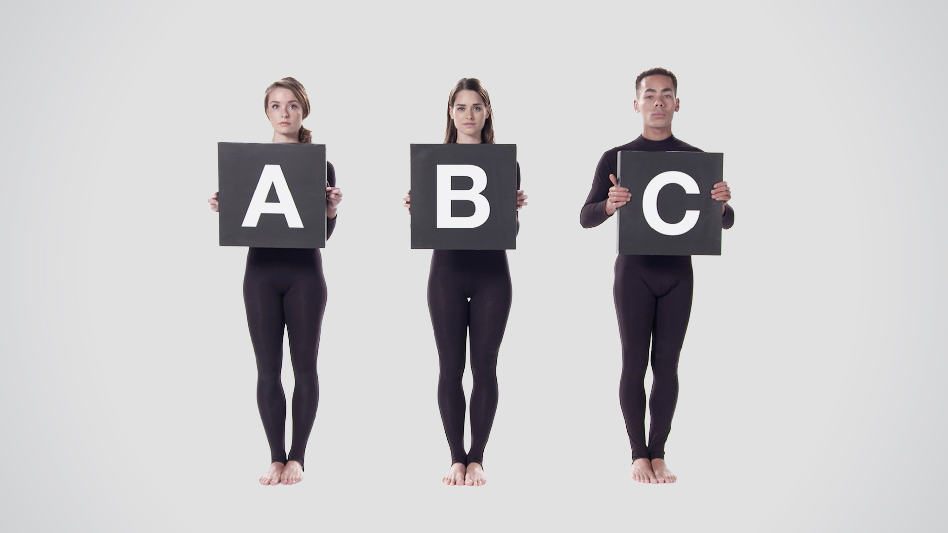 An image showing three people standing in a line. Each one is holding a board, with a letter printed onto it. The letters shown are A B and C.