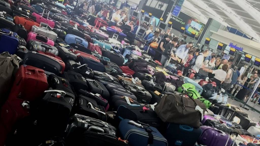 Piles of checked luggage on the floor in the Heathrow