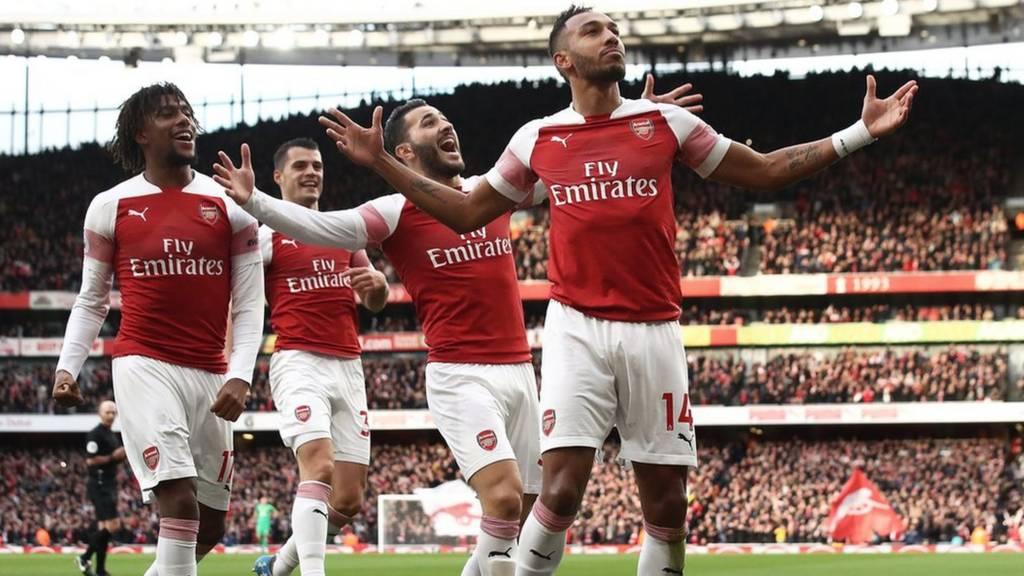 Arsenal players celebrate a goal against Tottenham