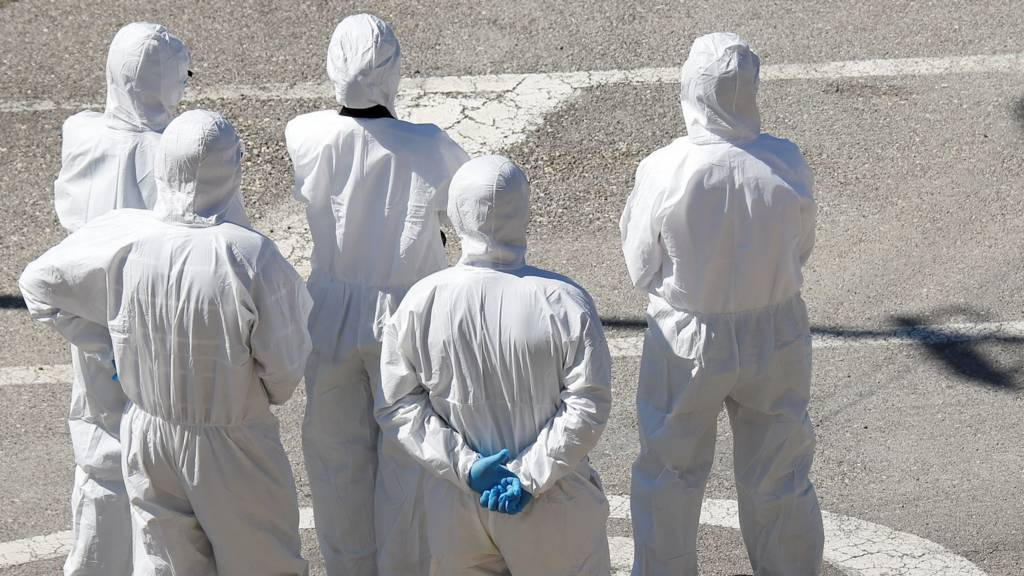 Police officials in protective clothing await migrants in Malta