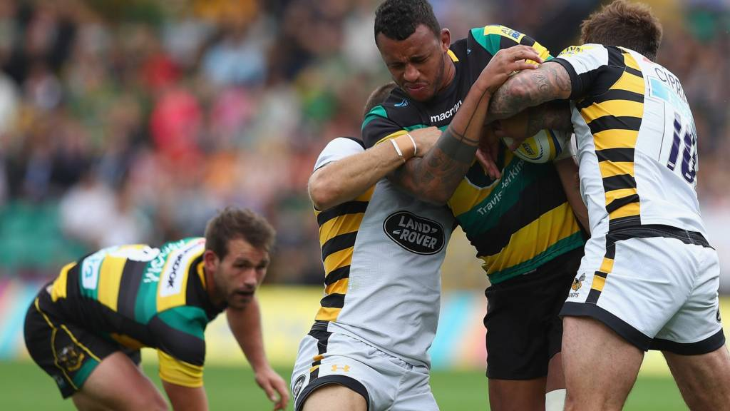 Northampton's Courtney Lawes wrapped up in a tackle by Wasps players