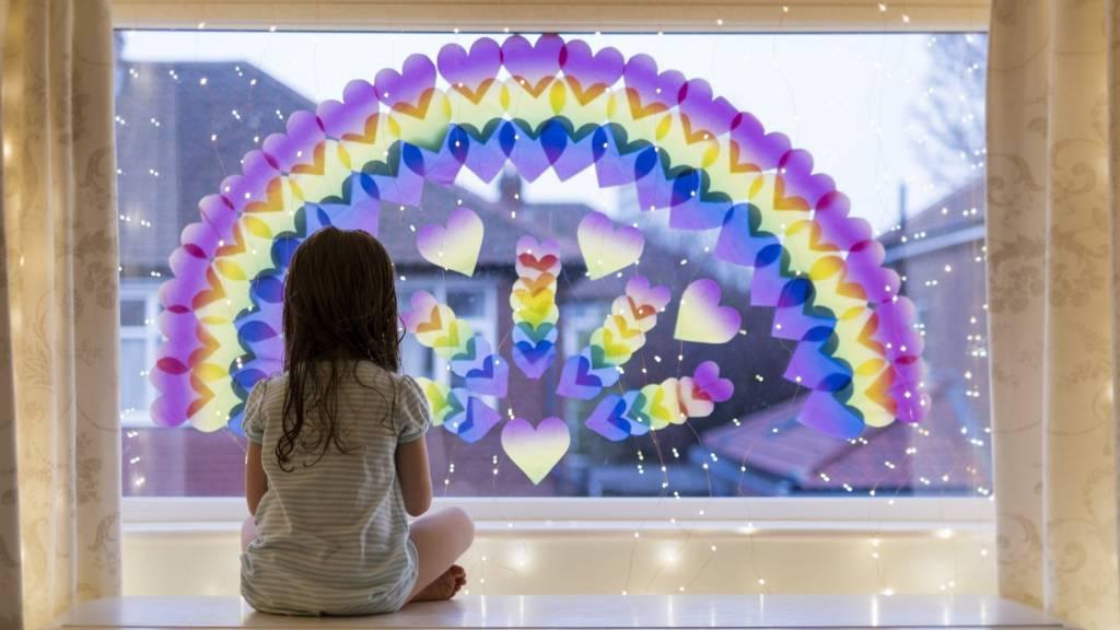 Girl sitting beside rainbow on window
