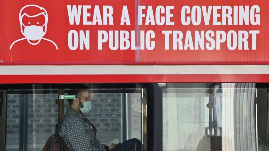 Man on bus with mask sign