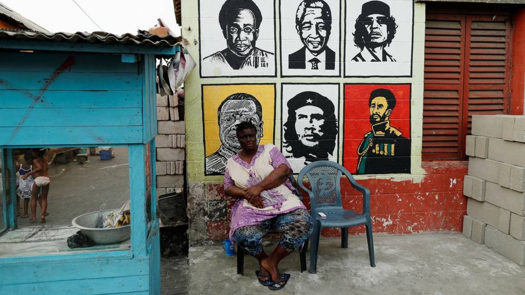A vendor sits next to a mural depicting African leaders in Ghana's capital, Accra.