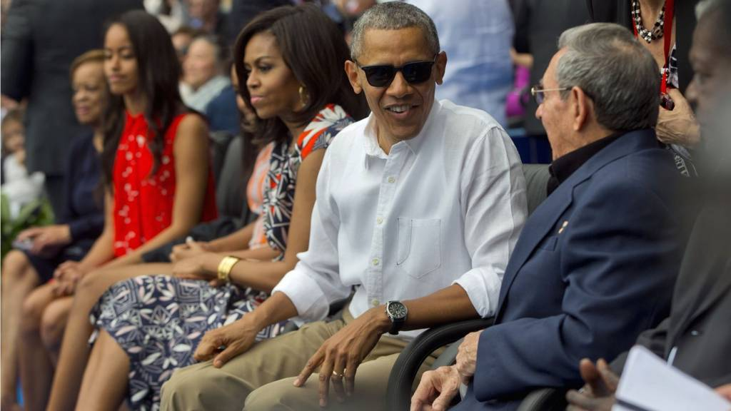 President Barack Obama, with members of his family, talks with Cuban President Raul Castro as they attend an exhibition baseball game between the Tampa Bay Rays and the Cuban National team at the Estadio Latinoamericano, Tuesday, 22 March 2016