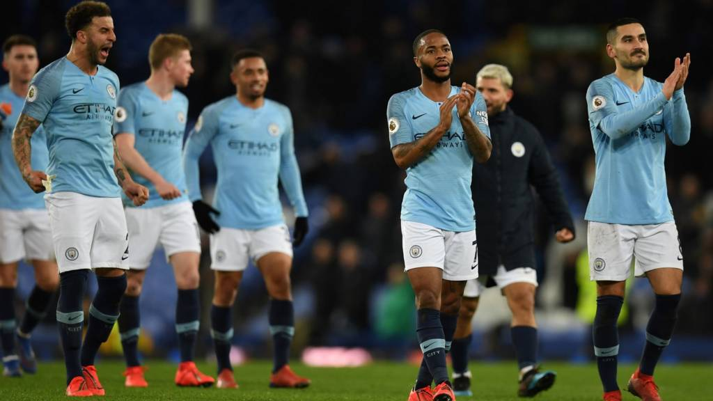 Manchester City players celebrate victory at Everton