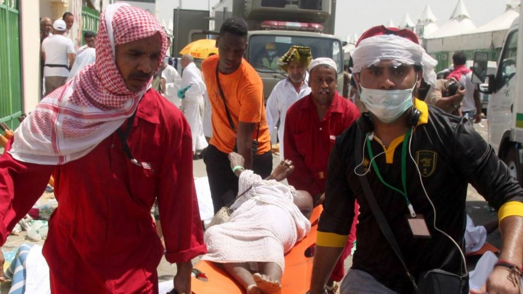 Saudi emergency personnel and pilgrims carry a wounded person at Mina on 24 September 2015