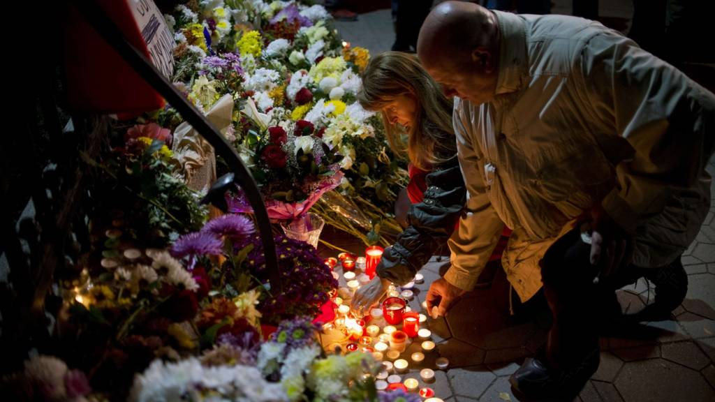 People light candles in Paris at a makeshift memorial