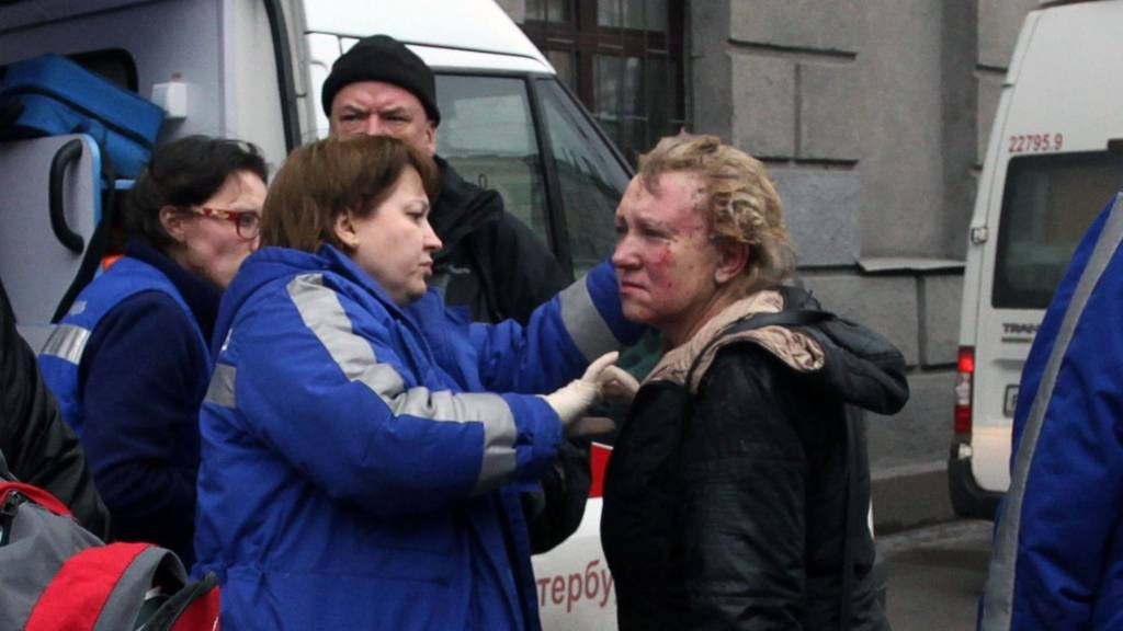 Medics help an injured woman outside Technological Institute metro station in Saint Petersburg