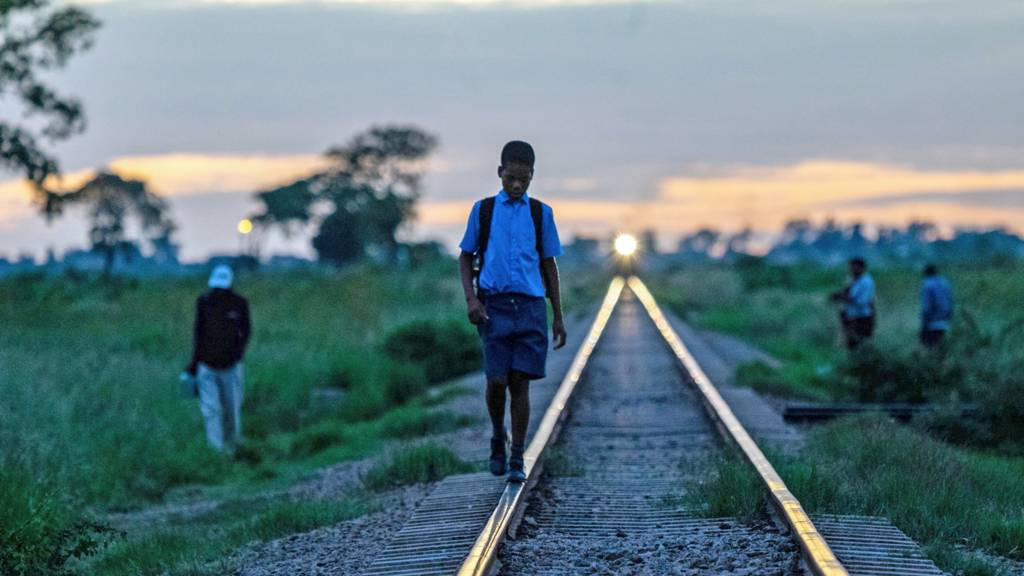 A child walking along a railway track in Zimbabwe - archive shot