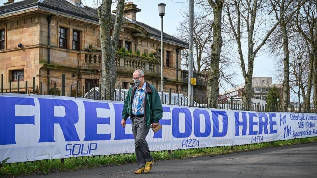 Man walking past free food sign in Glasgow