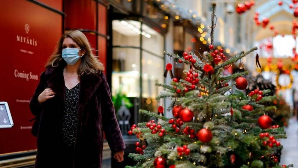 Woman wearing a mask walks past Christmas tree