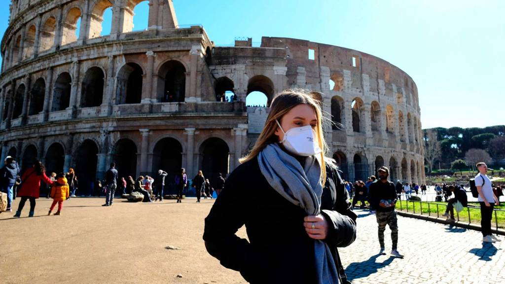 Tourist in mask outside Colosseum in Rome - 28 February