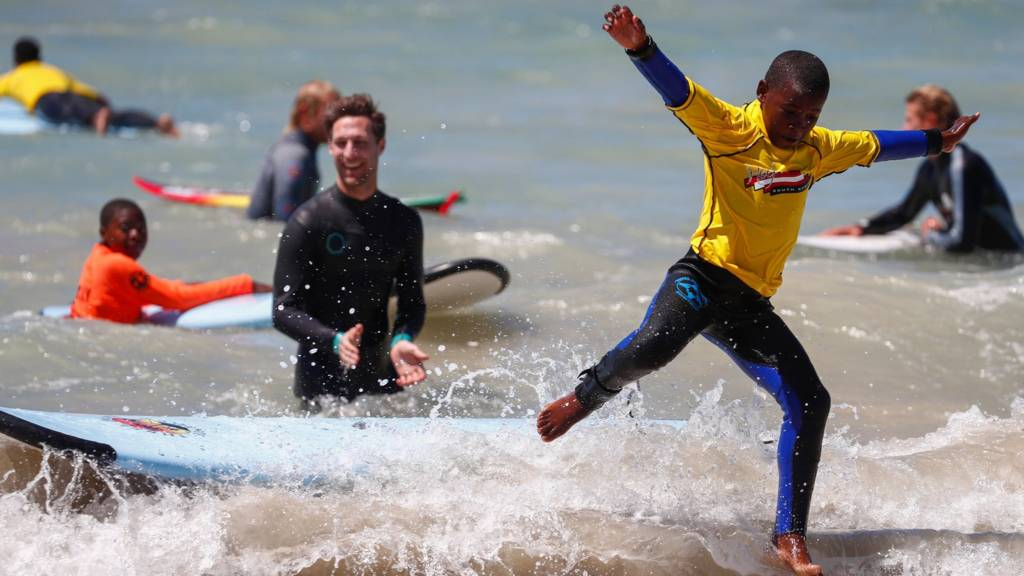 A South African child in the Waves For Change program wipes out whilst surfing during the Waves For Change Ocean Festival at Monwabisi beach in Cape Town, South Africa, 03 February 2018