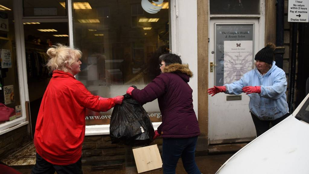 People help during the clean-up efforts at a business in Hebden Bridge after the flooding brought by Storm Ciara.