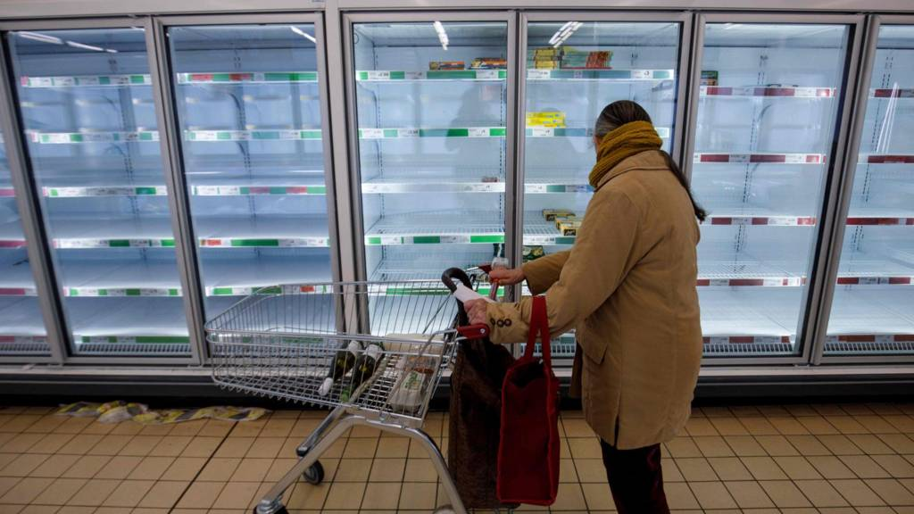 People shop in aisles with empty shelves in a Sainsbury's supermarket in Walthamstow