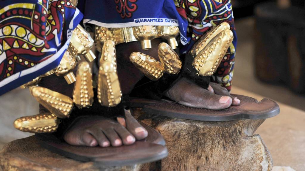 A closeup shows the shoes of the king of the N'Zima Kotoko people and first vice president of the Ivorian Commission on Dialog, Truth and Reconciliation, Awoulae Desire Amon Tanoe, as he sits on his throne