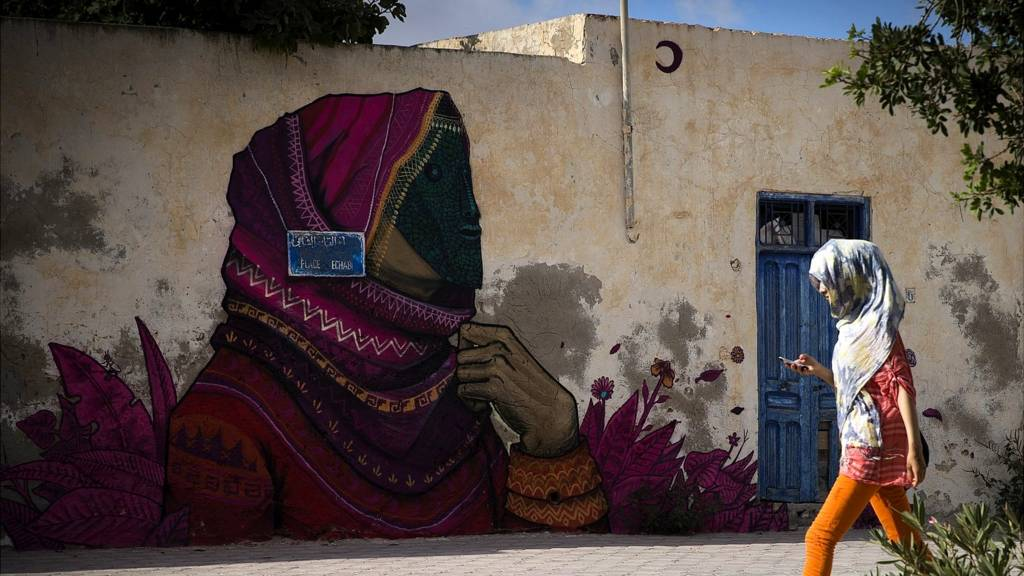A woman walks past a mural by Mexican artist SANER in the village of Erriadh, on the Tunisian island of Djerba, on August 7, 2014, as part of the artistic project 'Djerbahood'.