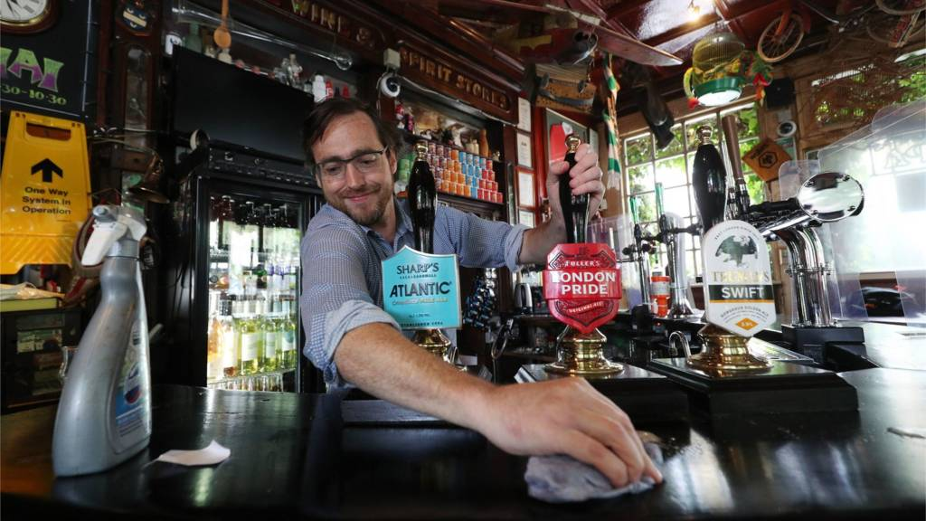 Manager Pat Fitzsimons cleaning the bar during final preparations at The Faltering Fullback pub in North London, 3 July