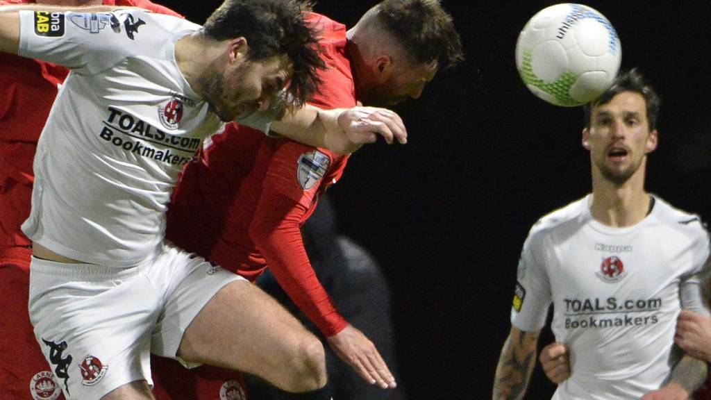 Crues midfielder Philip Lowry and Larne's Johnny McMurray challenge for the ball
