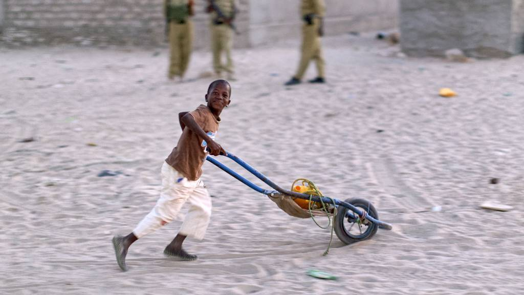 A Somali boy pushes a makeshift wheelbarrow across the sand in the former pirate town of Eyl, Somalia - March 2017