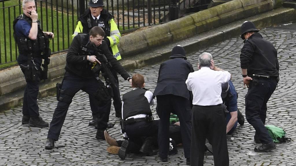Yerde yatan bir kişi e çevresinde polisler