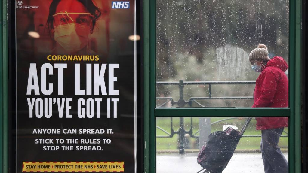 A woman by a government coronavirus poster at a bus stop in Bournemouth