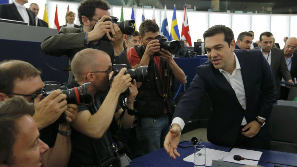 Alexis Tsipras (R) shakes hands with a Member of the European Parliament on 8 July