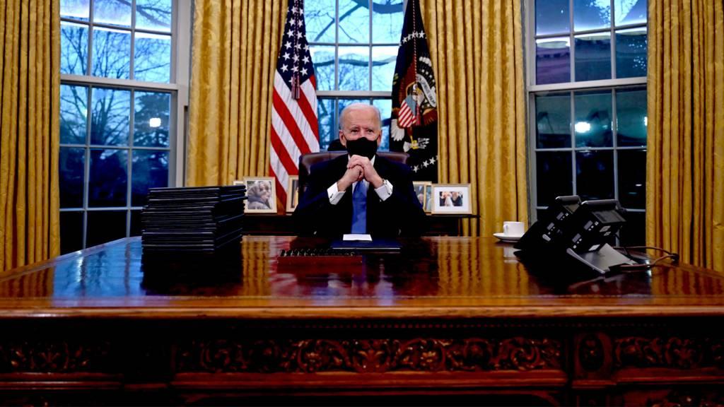 Joe Biden sits in the Oval Office