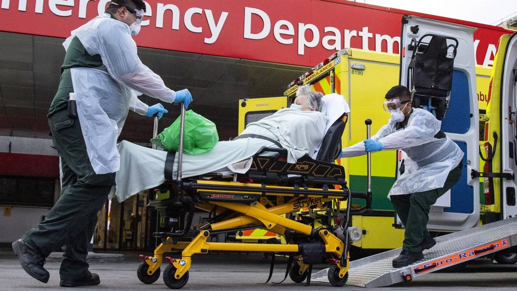 A woman with an unknown condition is helped from an ambulance at the St Thomas' Hospital