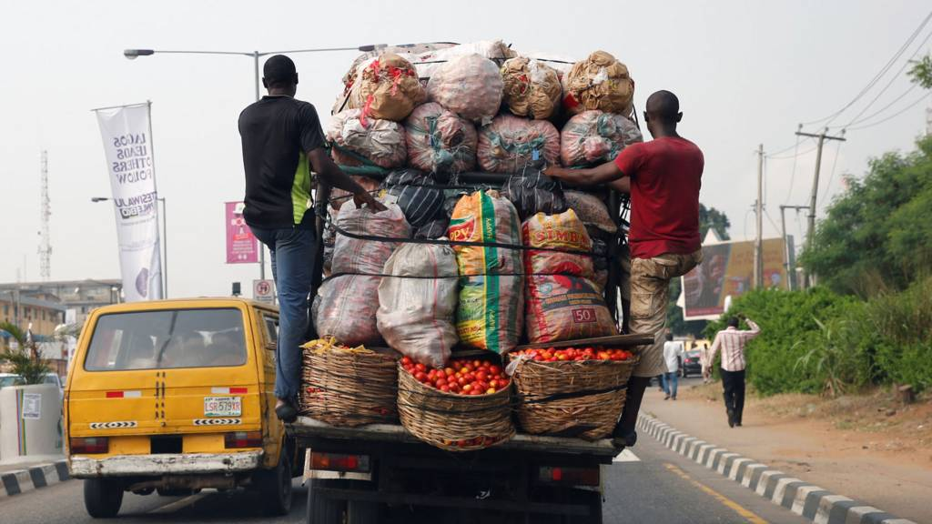 Men hang at the back of a truck loaded with farm produce along a road in Ikeja district in the commercial capital Lagos, Nigeria - 19 December 2016