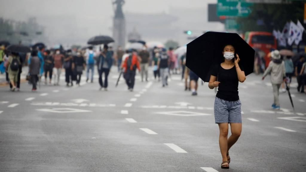 A woman wearing a mask walks past members of conservative civic groups in Seoul, South Korea