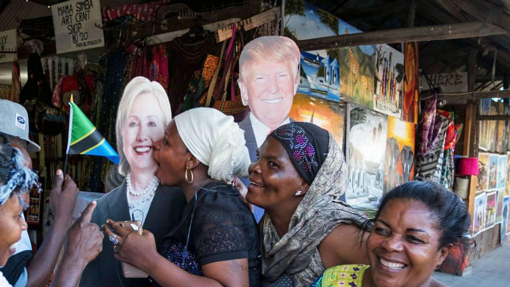 People pose with cut outs of US politicians Hillary Clinton and Donald Trump at a public relations campaign put on by the US Embassy in Dar es Salaam, Tanzania on 7 November 2016