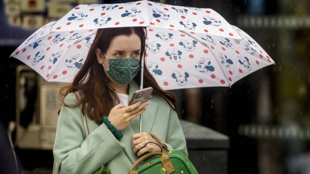 A woman walks through Belfast City Centre's shopping district wearing a face mask