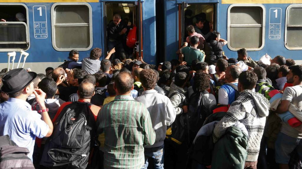 Migrants storm into a train at the Keleti train station in Budapest, Hungary - 3 September 2015