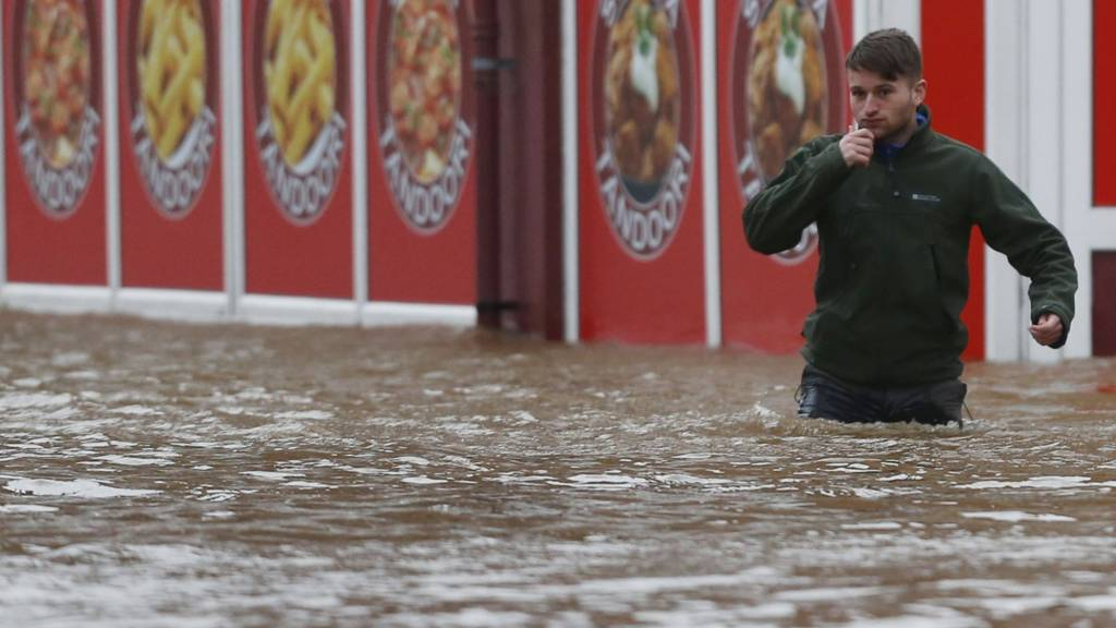 Man wades through flood water in Dumfries