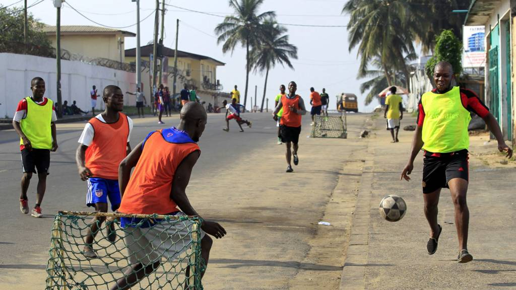 Liberians playing football on a street in Monrovia - January 2017
