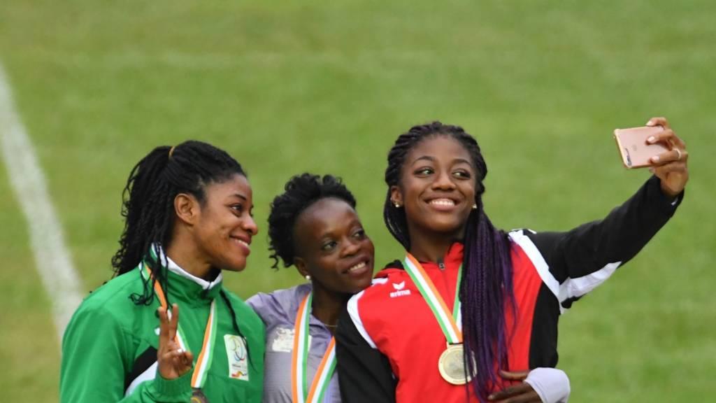 Medal-winning athletes pose for a selfie