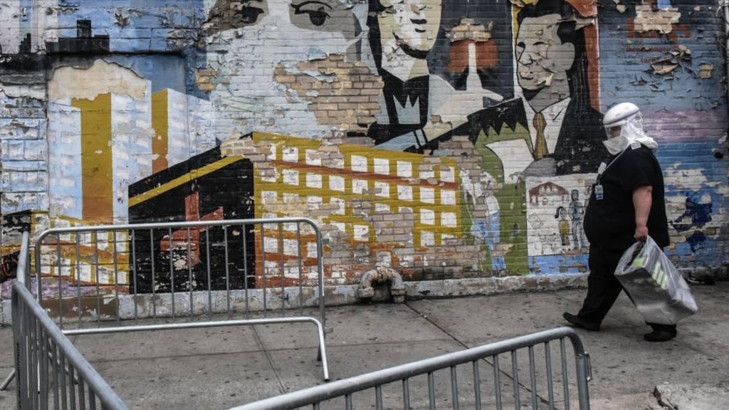 A health worker in PPE passes street art in Brooklyn