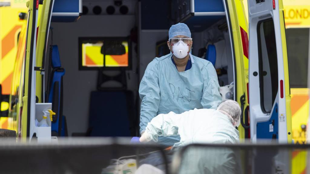 NHS workers in PPE take a patient with an unknown condition from an ambulance at St Thomas' Hospital on April 10, 2020 in London