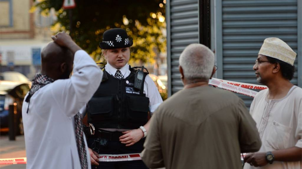 A police officer talks to local people at Finsbury Park in north London, where one man has died, eight people taken to hospital
