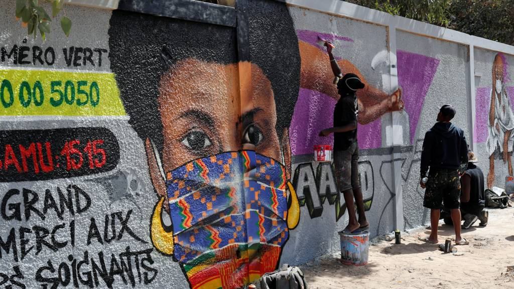 Graffiti artists at work painting a woman with a mask on a wall in Dakar, Senegal - 2020
