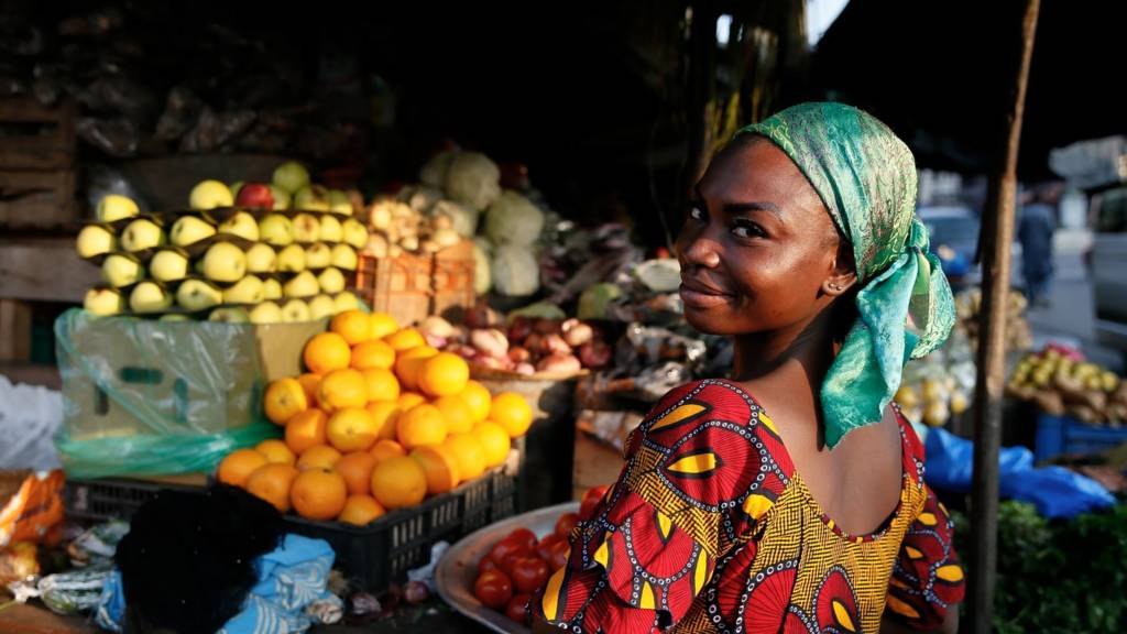 A fruit seller woman poses for a photo at a market in Abidjan, Ivory Coast on August 10, 2019